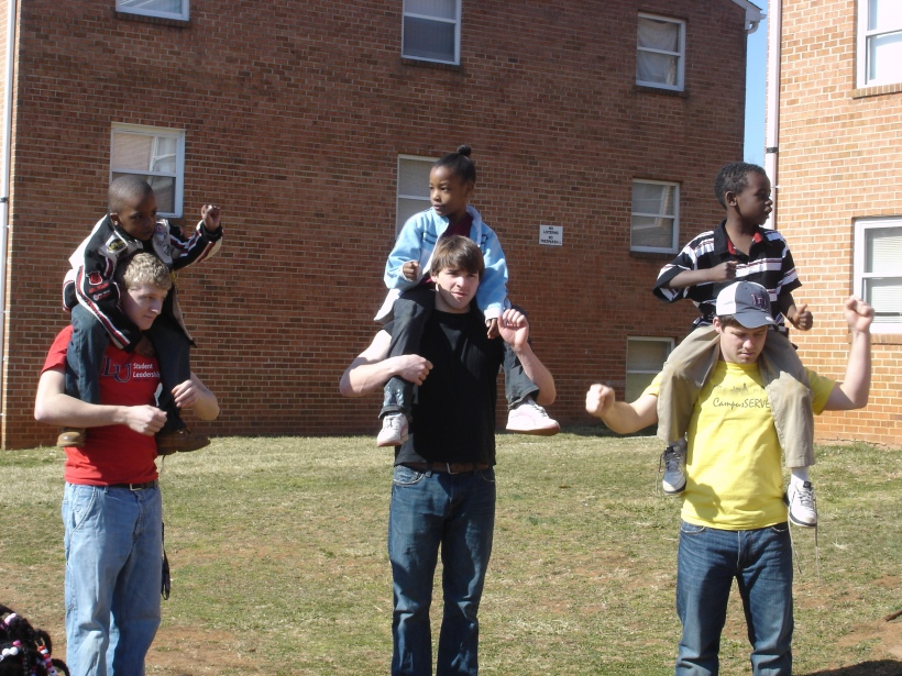 "The one with all the three guys with kids on their shoulders is when we were singing ""Father Abraham""  I think this truly represents Campus Serve because the kids constantly want to be put on people's shoulders or given piggy back rides.  Also it shows that Campus Serve is about having fun while learning about Bible stories."